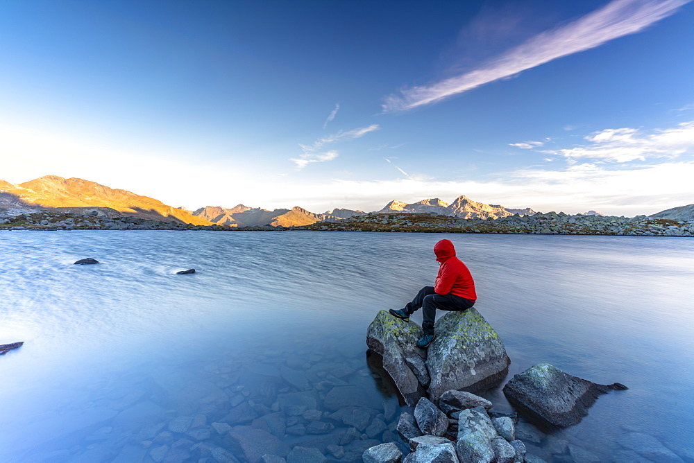 Hiker sitting on rocks on water edge of Laghi Azzurri (Bergsee) at dawn, Spluga Pass, Valle Spluga, Valtellina, Lombardy, Italy, Europe