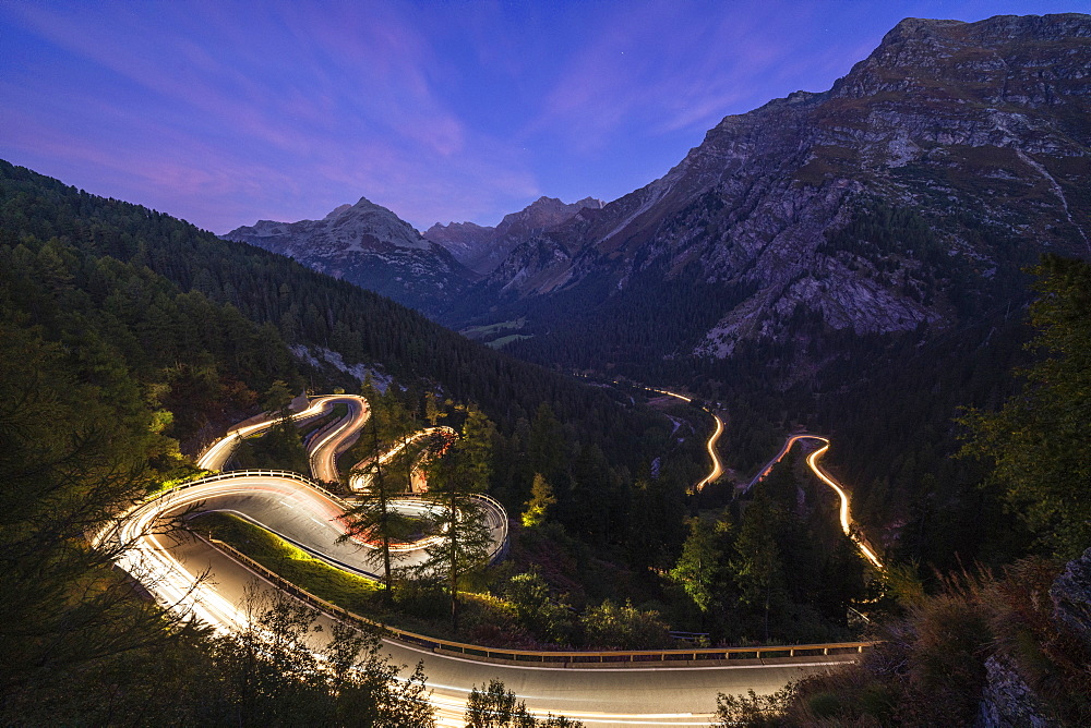 Car trails lights on narrow bends of Maloja Pass mountain road, Engadine, Canton of Graubunden, Switzerland, Europe