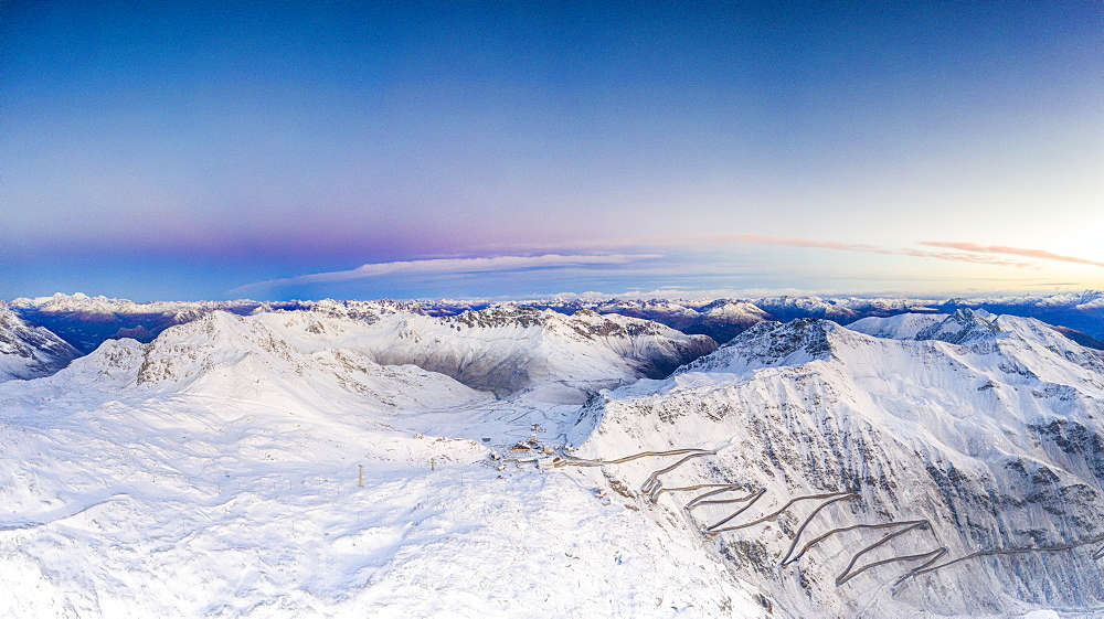Pano by drone of sunrise over the narrow bends of Stelvio Pass mountain road covered with snow, Bormio, Valtellina, Lombardy, Italy, Europe - 1179-4091