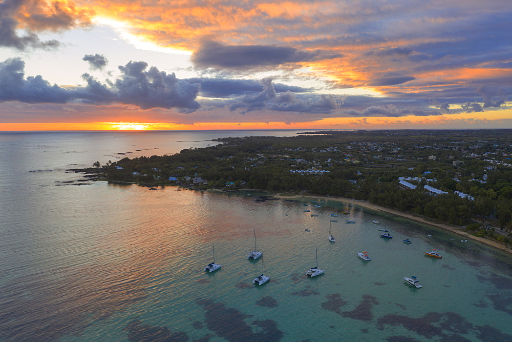 Orange sky at sunrise over the tropical beach and lagoon, aerial view, Grand Baie (Pereybere), Indian Ocean, Mauritius