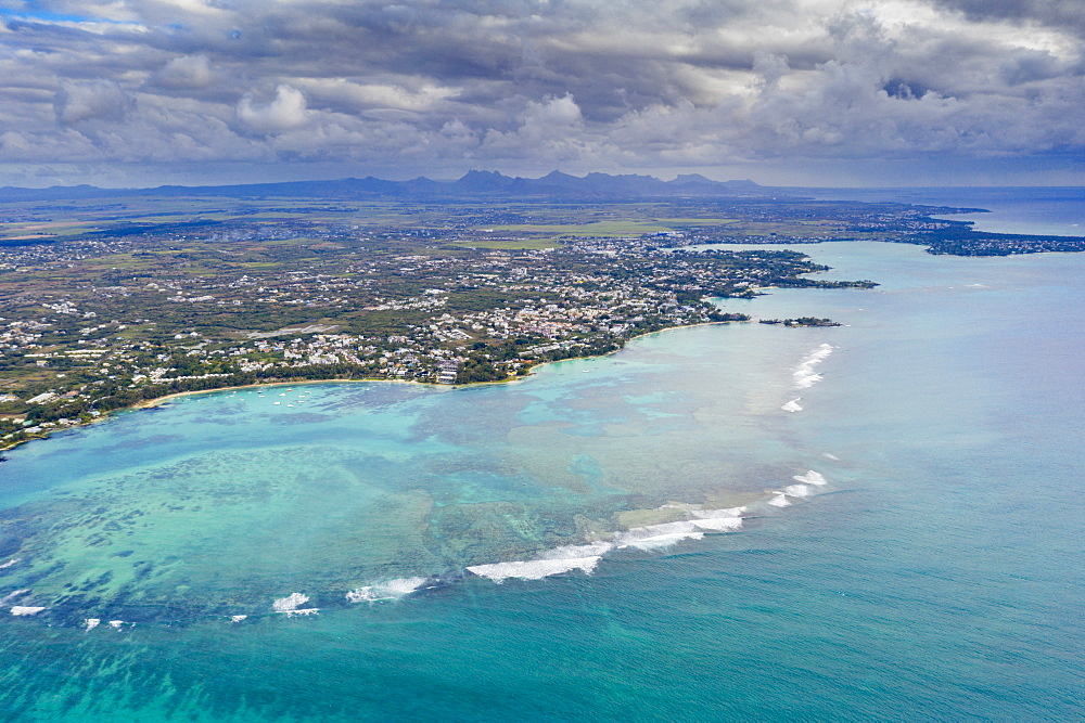 Dramatic sky over coral reef and inland, aerial view, Grand Baie (Pereybere), Indian Ocean, north-west coast, Mauritius (drone)