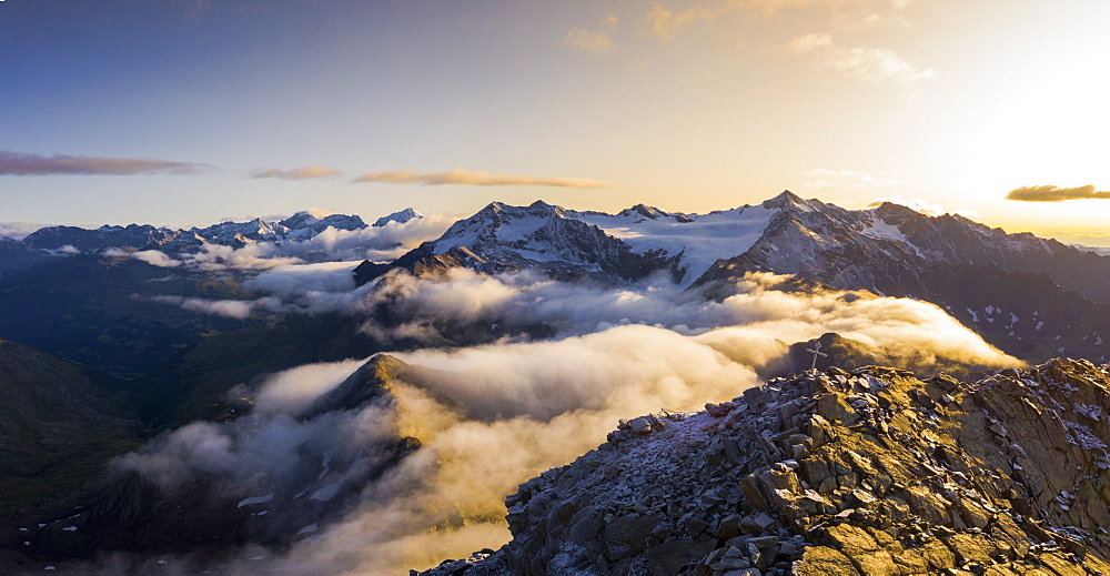 Aerial panoramic of low clouds covering Corno Tre Signori, Pizzo Tresero and Punta San Matteo peaks, Valtellina, Lombardy, Italy, Europe