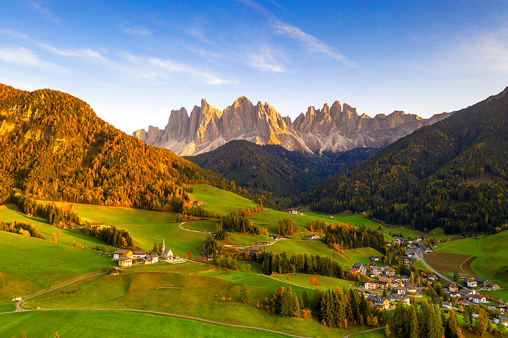 Sunset on the little village of Santa Magdalena and Odle peaks in autumn, aerial view, Funes, Dolomites, South Tyrol, Italy
