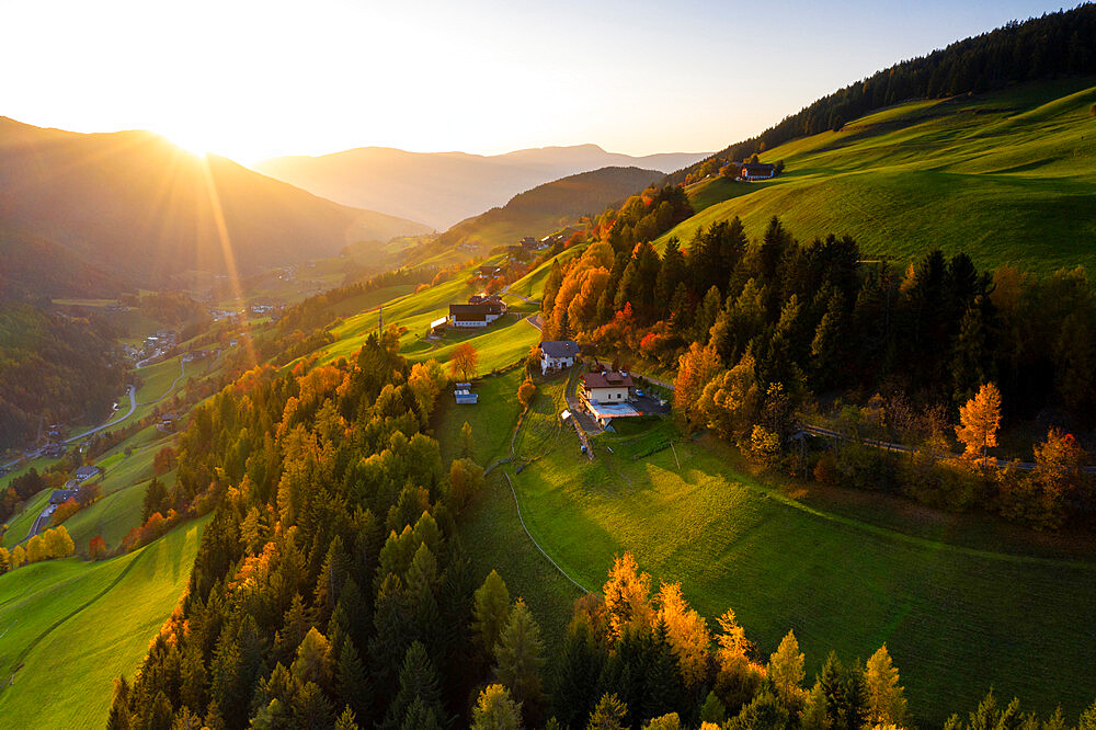 Sunbeam at sunset lighting the warm colors of autumn in Funes Valley, aerial view, Dolomites, Bolzano province, South Tyrol, Italy, Europe
