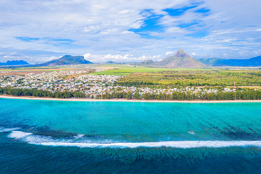 Waves crashing on Flic en Flac beach with Piton de la Petite Riviere Noire mountain, aerial view, Indian Ocean, Mauritius (drone