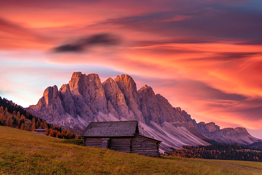 Sunrise over the Odle peaks and traditional hut in Gampen Alm in autumn, Funes Valley, Dolomites, Bolzano, South Tyrol, Italy
