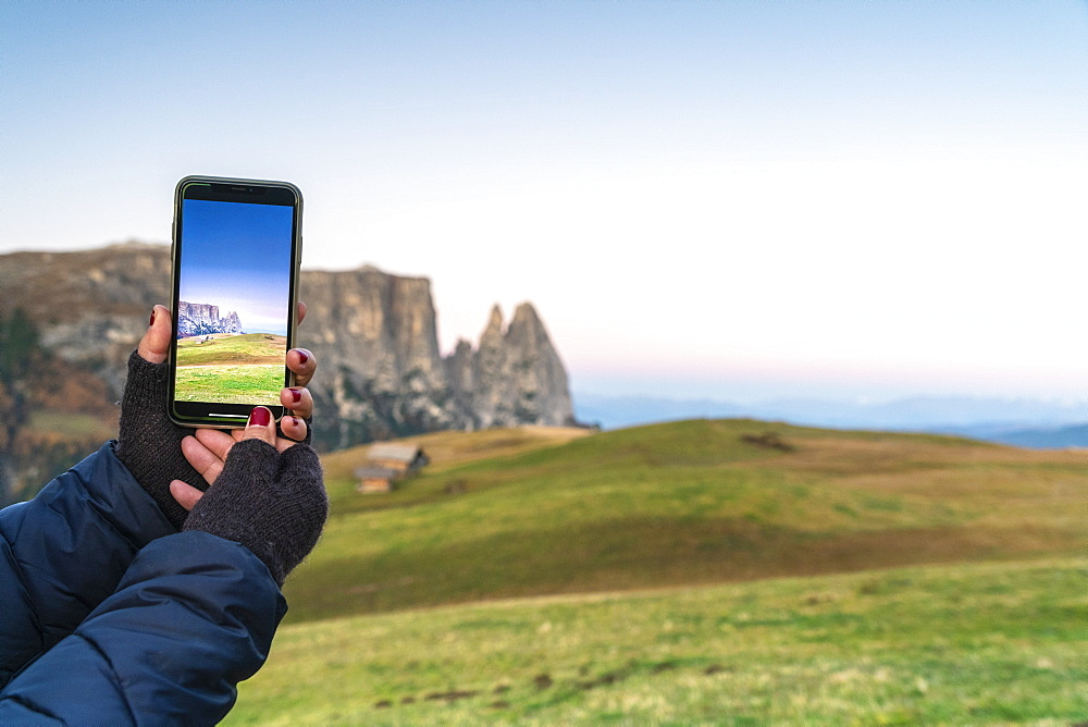 Personal perspective of woman photographing Sciliar peaks with smartphone, Alpe Siusi (Seiser Alm), Dolomites, South Tyrol, Italy, Europe