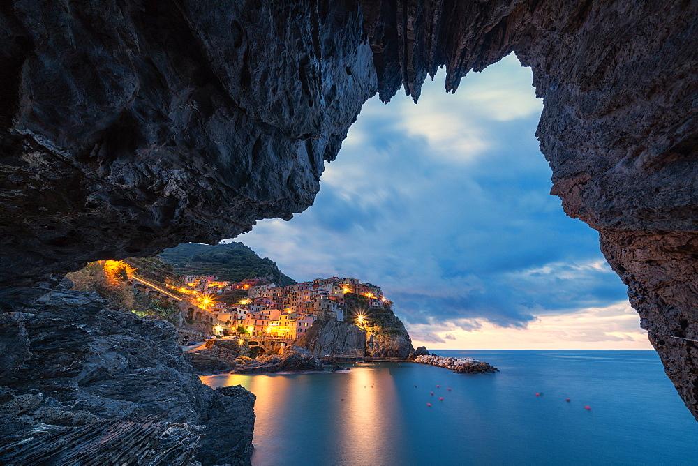 Manarola at dusk view from a grotto, Cinque Terre, UNESCO World Heritage Site, La Spezia province, Liguria, Italy, Europe