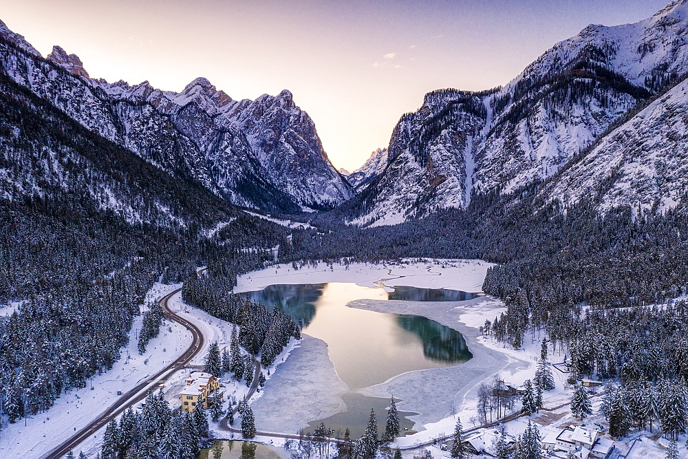 Sunrise over the icy Lake Dobbiaco and woods in winter, Dobbiaco, Val Pusteria, Dolomites, Bolzano province, South Tyrol, Italy, Europe