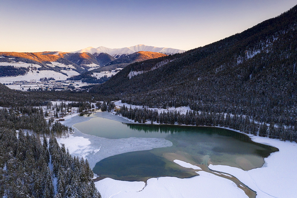 Sunrise over the village of Dobbiaco and frozen lake, Val Pusteria, Dolomites, Bolzano province, South Tyrol, Italy