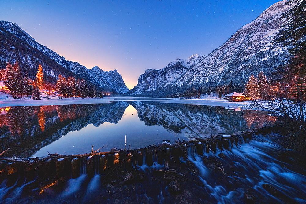 Dusk lights on the snowy peaks mirrored in Lake Dobbiaco, Val Pusteria, Dolomites, Bolzano province, South Tyrol, Italy