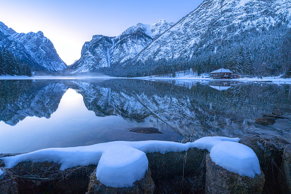 Winter dusk over Lake Dobbiaco surrounded by snow, Dobbiaco, Val Pusteria, Dolomites, Bolzano province, South Tyrol, Italy