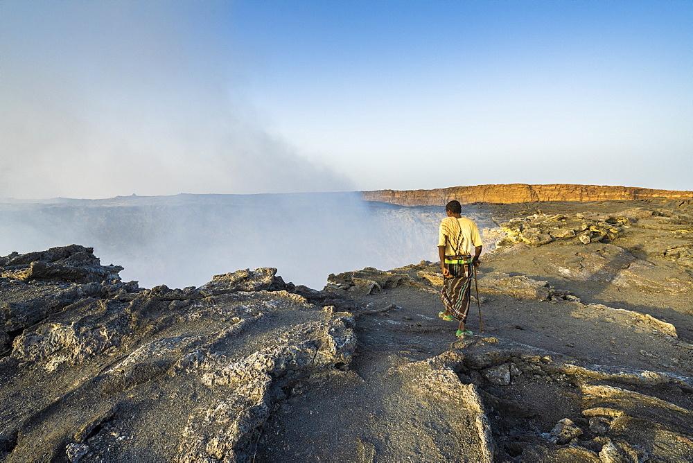 Afar man looking down to Erta Ale volcano caldera, Danakil Depression, Afar Region, Ethiopia, Africa