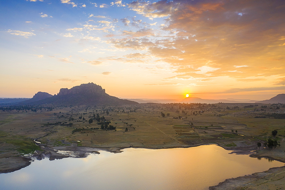 Sunrise lit the small lake and Gheralta Mountains in background, aerial view, Dugem, Tigray Region, Ethiopia, Africa (drone)