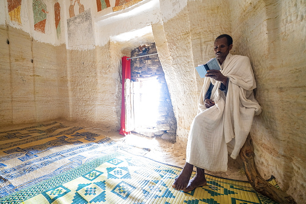 Priest holding the prayer book in the Orthodox Christian Daniel Korkor church, Gheralta Mountains, Tigray Region, Ethiopia