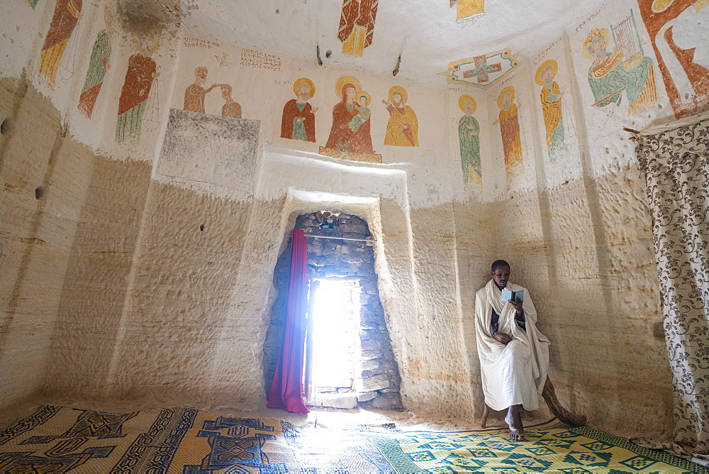 Orthodox Christian priest holding the prayer book inside Daniel Korkor church, Gheralta Mountains, Tigray Region, Ethiopia, Africa