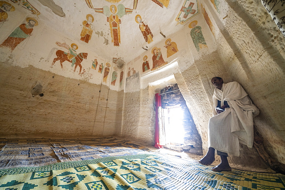 Orthodox priest meditating inside Daniel Korkor rock-hewn church, Gheralta Mountains, Tigray Region, Ethiopia, Africa