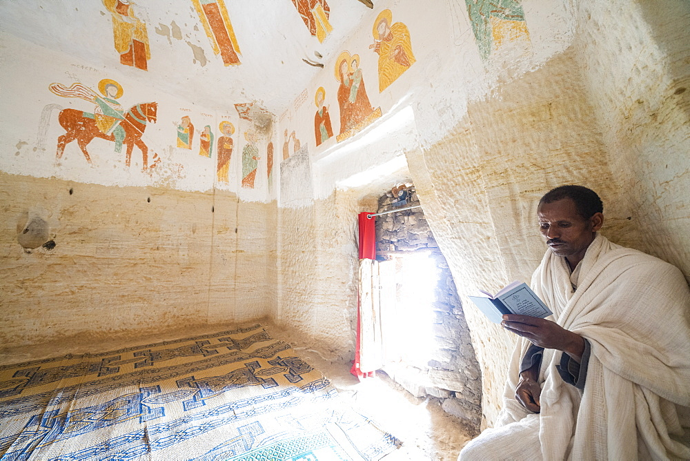 Priest holding the prayer book in the Orthodox Christian Daniel Korkor church, Gheralta Mountains, Tigray Region, Ethiopia, Africa