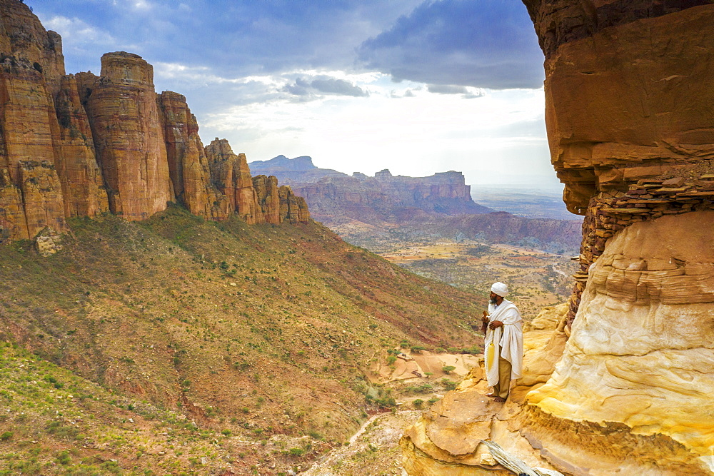 Orthodox priest admiring Gheralta Mountains from the entrance of Abuna Yemata Guh church, Tigray Region, Ethiopia, Africa