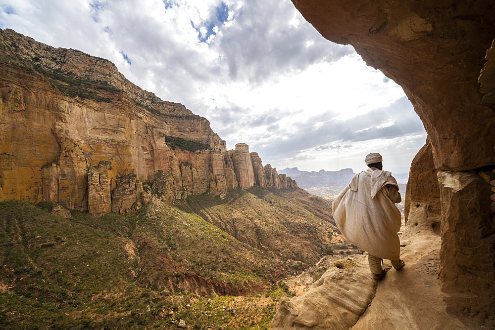 Rear view of priest walking on access trail to the rock-hewn Abuna Yemata Guh church, Gheralta Mountains,Tigray region, Ethiopia