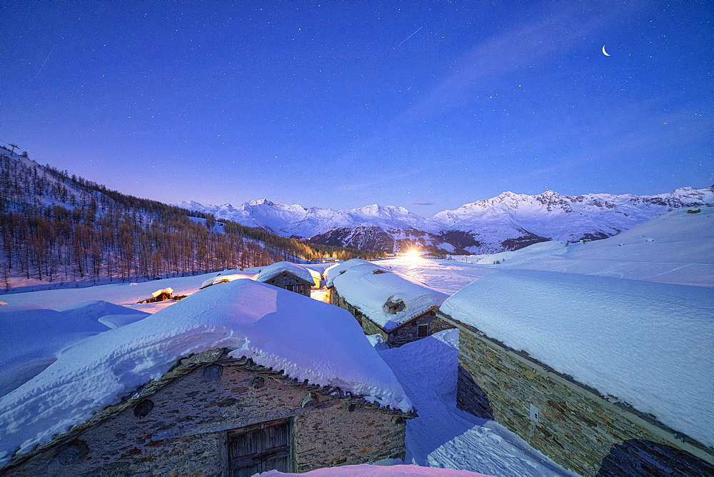 Groppera stone huts covered with snow during a starry night, Madesimo, Valchiavenna, Valtellina, Lombardy, Italy