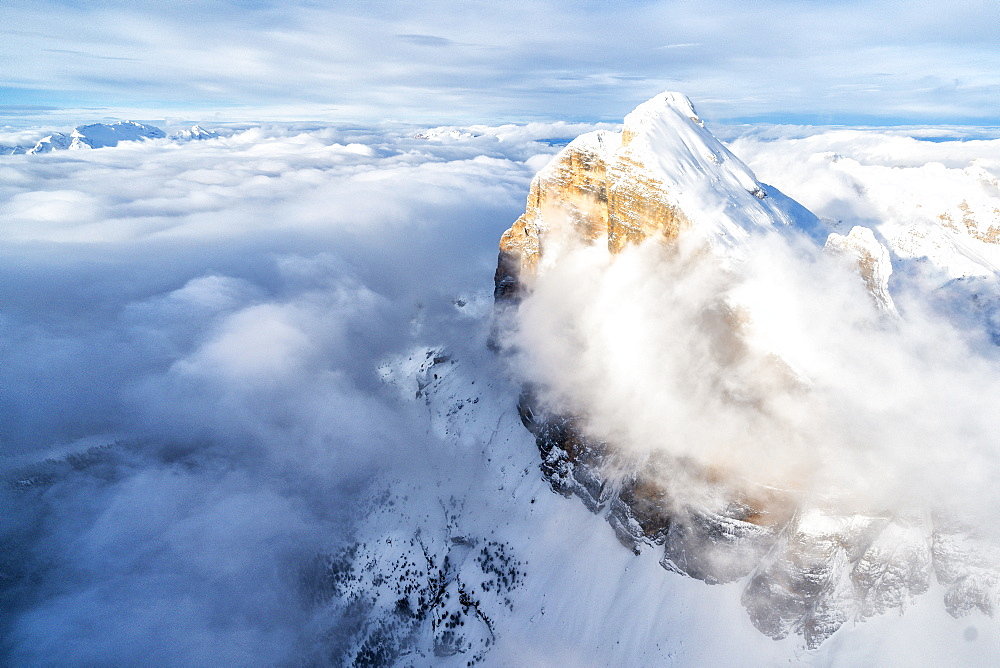 Snow covered Tofana di Rozes above the clouds, aerial view, Dolomites, Belluno province, Veneto, Italy