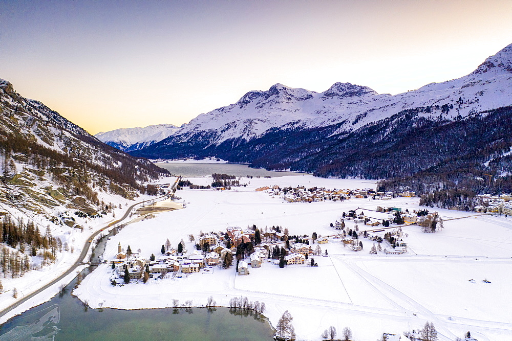 Snowy village of Segl (Sils im Engadin) on shores of Lake Sils at dawn, Engadin, canton of Graubunden, Switzerland