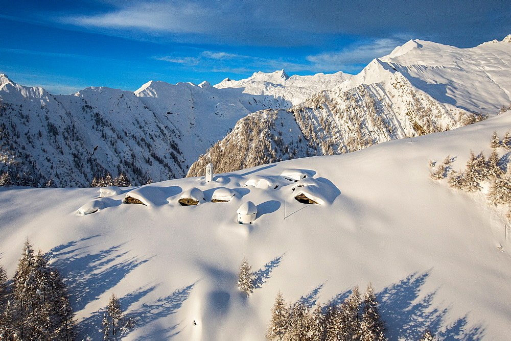 A little village at the foot of Alpe Scima, with its mountain huts and church covered in snow, Valchiavenna, Lombardy, Italy, Europe