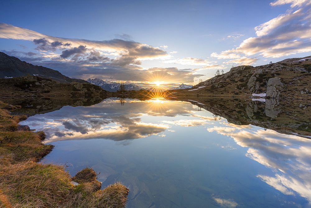 Sunburst over the clear waters of lake Zana during sunrise, Valmalenco, Sondrio province, Valtellina, Lombardy, Italy, Europe