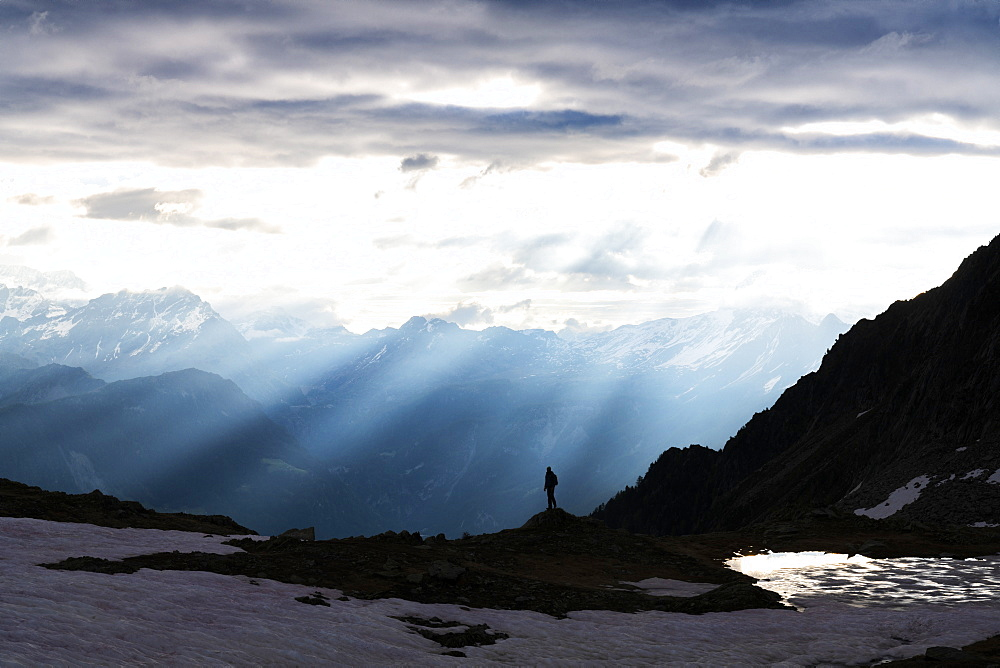 Silhouette of lone hiker admiring the sun rays at dawn over lake Zana, Valmalenco, Valtellina, Lombardy, Italy, Europe