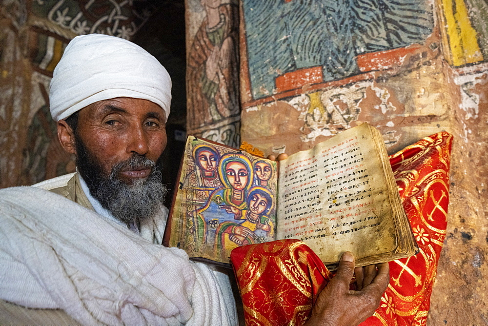 Orthodox priest holding an old Bible with hand-painted saints, Abuna Yemata Guh church, Gheralta Mountains,Tigray Region, Ethiopia, Africa