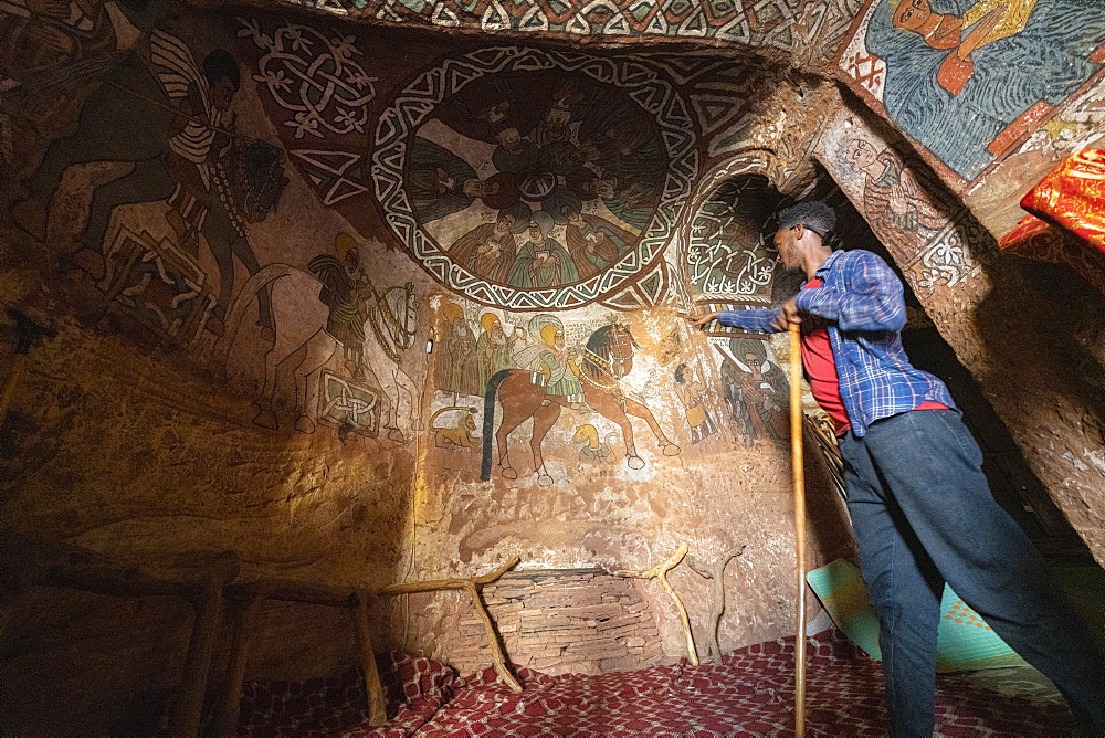 Local guide showing fresco and paintings inside Abuna Yemata Guh church, Gheralta Mountains, Tigray Region, Ethiopia, Africa