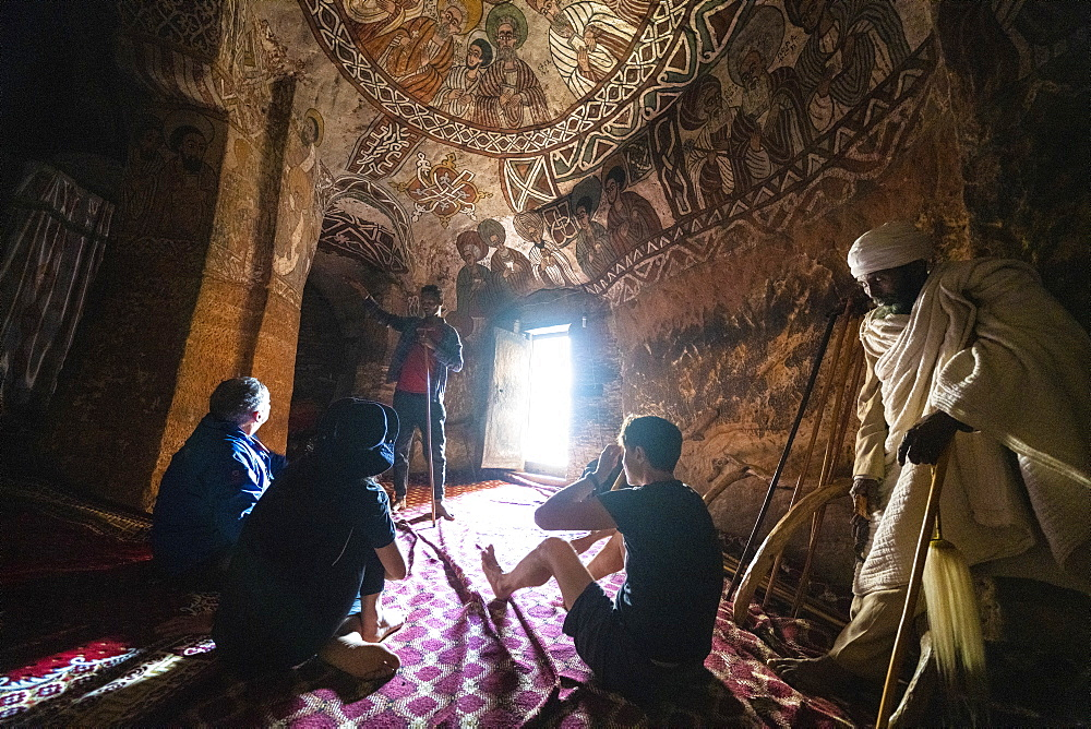Tourists admiring fresco and paintings inside Abuna Yemata Guh church, Gheralta Mountains, Tigray Region, Ethiopia, Africa