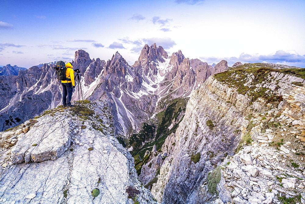 Man on top of rocks photographing Cadini di Misurina at sunrise, Dolomites, Belluno province, Veneto, Italy, Europe - 1179-4654