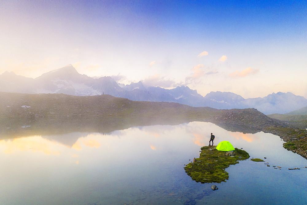 Hiker man with tent admiring a misty sunrise over mountains from Obere Schwarziseeli lake, Furka Pass, Canton Uri, Switzerland, Europe - 1179-4682
