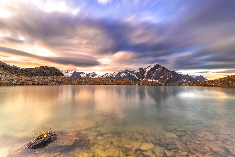 Dramatic sky at sunrise over Tresero peak reflected in lake Manzina, Valfurva, Valtellina, Sondrio province, Lombardy, Italy - 1179-4788
