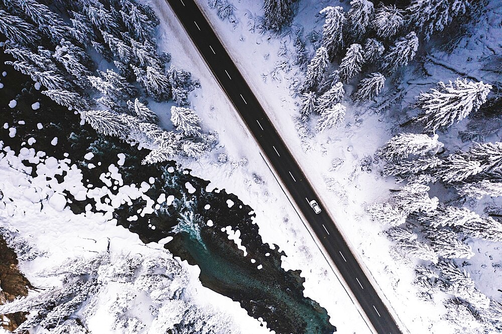 Car traveling on snowy mountain road across frozen river and woods, aerial view, Switzerland, Europe - 1179-4901
