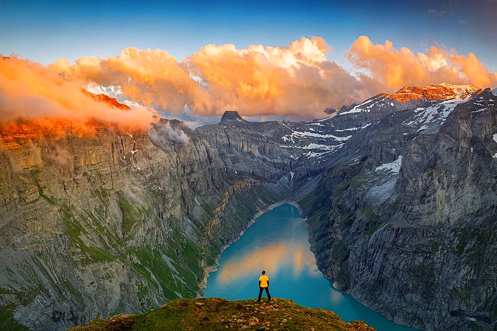 Man standing on rocks looking at clouds at sunset over lake Limmernsee, aerial view, Canton of Glarus, Switzerland, Europe - 1179-4938