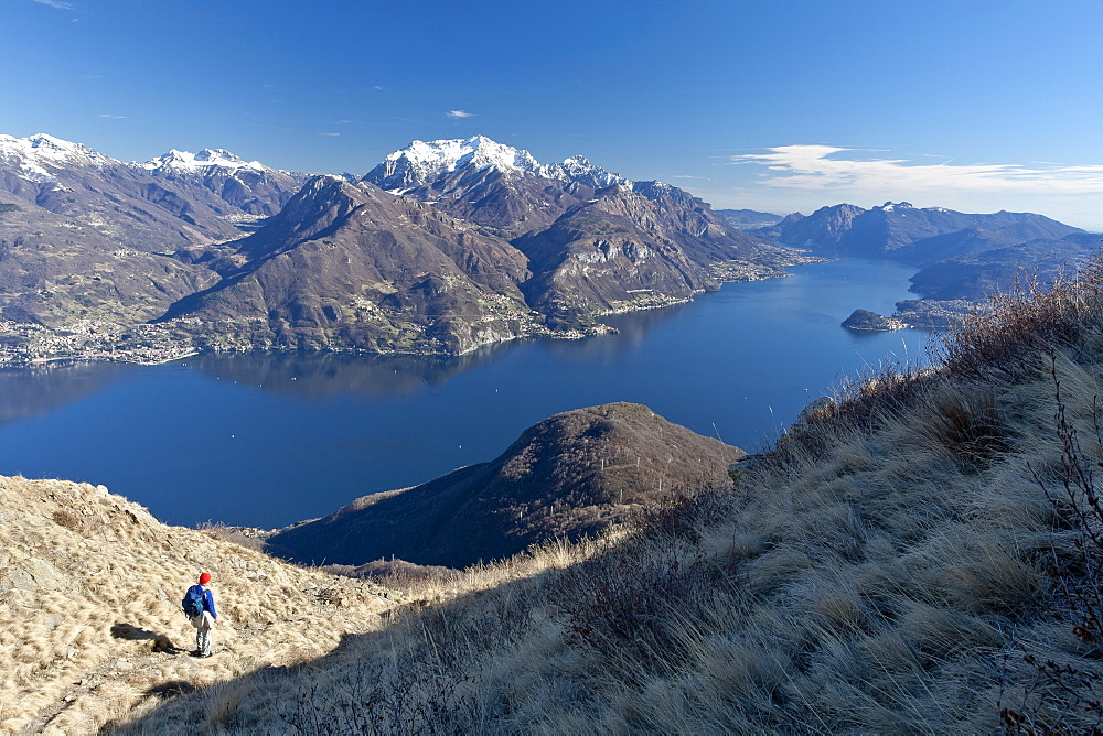 A tourist contemplating the landscape of Lake Como from a path in the High Route of Monti Lariani, with the village of Bellagio, Lombardy, Italy, Europe