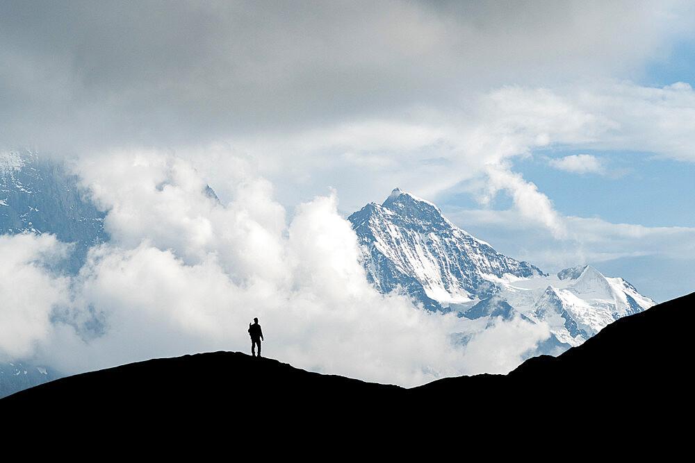 Silhouette of hiker man admiring Jungfrau mountain peak from First, Grindelwald, Bernese Alps, Canton of Bern, Switzerland - 1179-5005