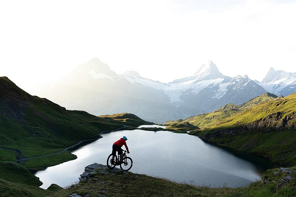 Mountain biker riding downhill at Bachalpsee lake at dawn, Grindelwald, Bernese Oberland, Bern Canton, Switzerland - 1179-5014