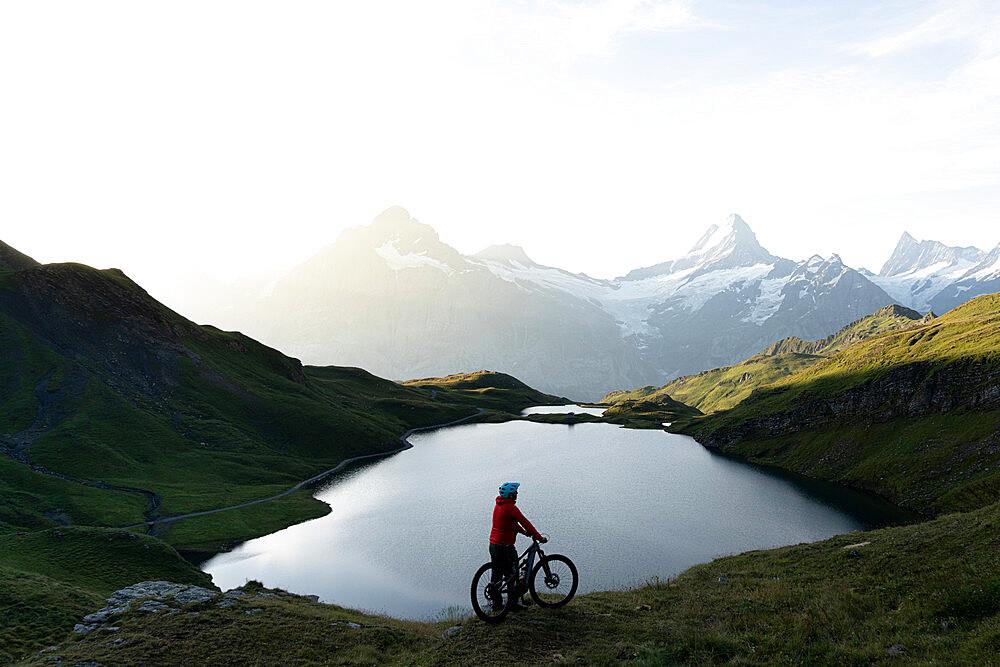 Hiker with mountain bike admiring sunrise over Bachalpsee lake, Grindelwald, Bernese Oberland, Bern Canton, Switzerland - 1179-5016