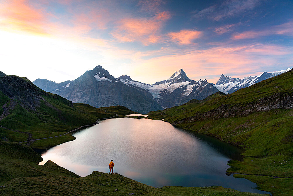 Hiker admiring sunrise from the shores of Bachalpsee lake, Grindelwald, Bernese Oberland, Bern Canton, Switzerland - 1179-5017