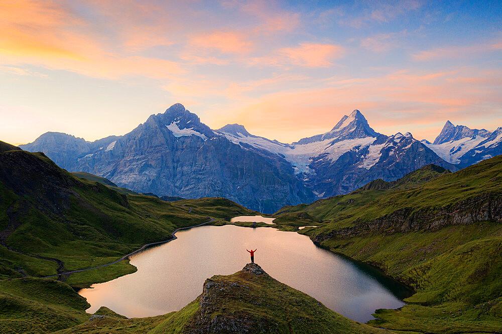 Cheerful hiker admiring Wetterhorn, Schreckhorn and Finsteraarhorn from Bachalpsee at dawn, Bernese Oberland, Switzerland - 1179-5021