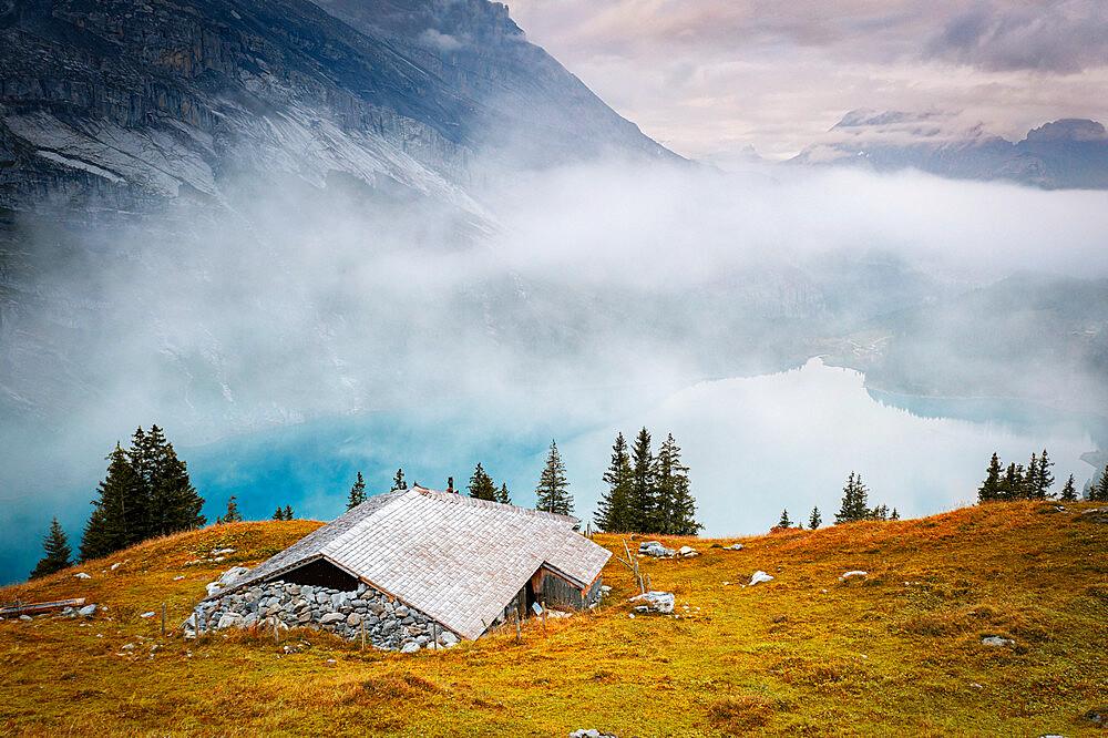 Hut on mountain ridge above lake Oeschinensee covered by mist, Bernese Oberland, Kandersteg, canton of Bern, Switzerland - 1179-5040
