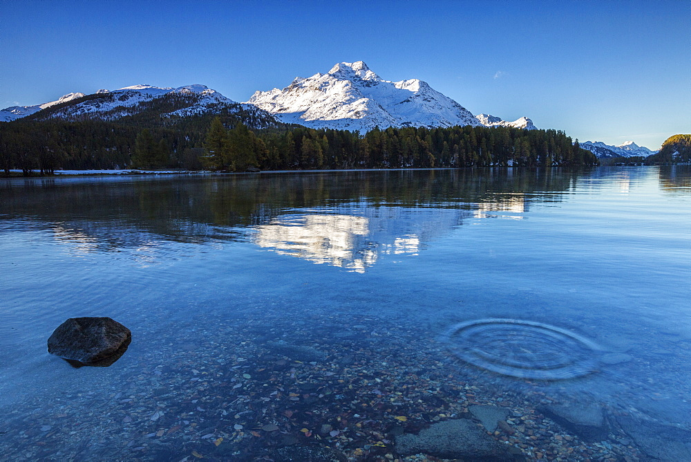 Dawn illuminates the snowy peaks reflected in the calm waters of Lake Sils, Engadine, Canton of Graubunden, Switzerland, Europe