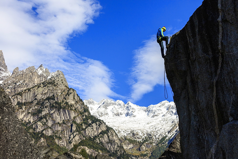 Climber on steep rock face in the background blue sky and snowy peaks of the Alps, Masino Valley, Valtellina, Lombardy, Italy, Europe