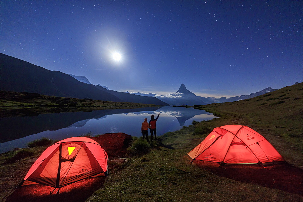 Hikers admire Matterhorn reflected in Lake Stellisee on a starry night of full moon, Zermatt, Canton of Valais, Swiss Alps, Switzerland, Europe