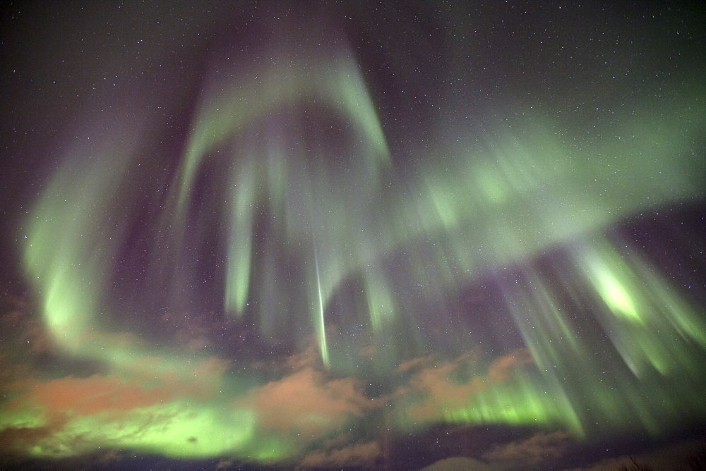 The shapes of green light of the Aurora Borealis color the sky, Lyngen Alps, Troms, Lapland, Norway, Scandinavia, Europe
