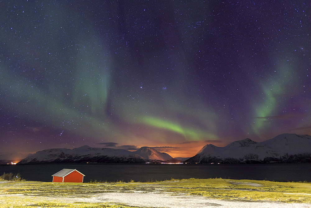 Northern Lights illuminates the wooden cabin at Svensby, Lyngen Alps, Troms, Lapland, Norway, Scandinavia, Europe